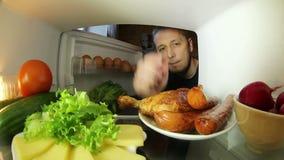 Mann, der nach Lebensmittel im Kühlschrank sucht Die Wahl zwischen Fleisch oder Gemüse stock footage