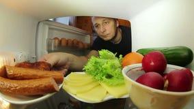 Mann, der nach Lebensmittel im Kühlschrank sucht Die Wahl zwischen Fleisch oder Gemüse stock video