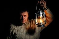 Mann in der Nacht mit einer brennenden Kerosinlampe Stockbild