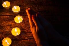 Mann, der nahe bei den Kerzen auf Holztisch betet Stockbilder