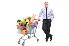 Mann, der nahe bei einem Einkaufswagen mit Lebensmittelgeschäften aufwirft Lizenzfreie Stockfotografie