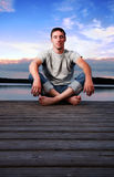 Mann, der nahe dem Wasser am Abend sitzt Lizenzfreie Stockbilder
