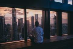 Mann, der nahe einem Fenster an der Spitze eines hohen Gebäudes mit der Ansicht von hohen Gebäuden der städtischen Stadt sitzt lizenzfreies stockfoto