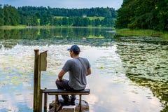 Mann, der nahe See stillsteht Stockbilder