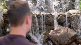 Mann, der nahe Wasserfall am Berg träumt Wanderer, der nahen Gebirgswasserfall steht stock video