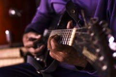 Mann, der nahes hohes der Gitarre spielt Stockfotos