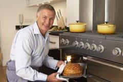 Mann, der Nahrung aus dem Ofen heraus nimmt stockbild