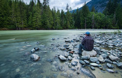 Mann, der neben Fluss-Landschaft sitzt stockfotografie