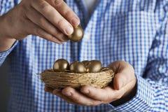 Mann, der Nest voll von den goldenen Eiern hält Stockfoto