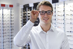 Mann, der neue Gläser an den Optikern wählt Stockfoto