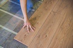 Mann, der neuen hölzernen lamellenförmig angeordneten Bodenbelag installiert Infrarotbodenhitze stockbild