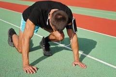 Mann in der niedrigen Anfangsposition auf Stadion Athlet in Ausgangsposition Männlicher Läufer, der Musik am MP3-Player oder am H Lizenzfreies Stockfoto