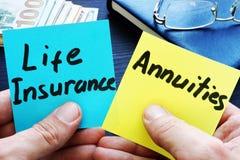 Mann, der Notizstöcke hält Lebensversicherung gegen rentenpapiere stockfoto