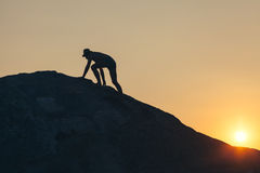 Mann, der oben den Hügel klettert Lizenzfreie Stockfotografie