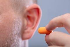 Mann, der Ohrenpfropfen in sein Ohr einf?gt stockbilder