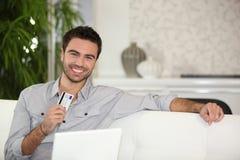 Mann, der online Kreditkarte verwendet Stockbild