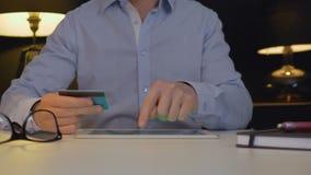 Mann, der online mit Tablette zahlt stock video footage