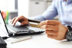 Mann, der online unter Verwendung des Laptops mit Kreditkarte kauft Stockfotos