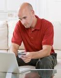 Mann, der Onlinekauf auf Laptop abschließt Stockbild