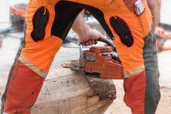 Mann in der orange Sicherheitskleidung von hinten, die Barke von entfernend lizenzfreies stockfoto