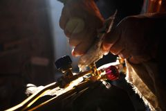 Mann, der oxy Acetylenfackel-Propanwerkzeuge für den Schnitt des Metalls in seiner Werkstatt säubert Lizenzfreies Stockbild