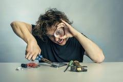 Mann in der Panik mit seinen Telefonreparaturen Stockfotografie