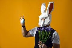 Mann in der Papierkaninchenmaske hält einen Blumenstrauß von Irisblumen auf einem gelben Studiohintergrund lizenzfreie stockfotos