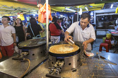 Mann, der Pfannkuchen an PJ Pasar Malam kocht Stockfotografie
