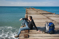Mann, der am Pier sitzt stockfotos