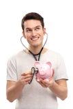 Mann, der piggy Querneigung mit Stethoskop überprüft Stockfotos