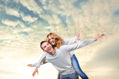 Mann, der piggyback der Freundin Fahrt unter dem Himmel gibt stockfotografie