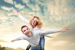 Mann, der piggyback der Freundin Fahrt unter dem Himmel gibt lizenzfreie stockfotos
