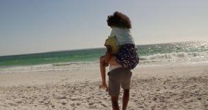 Mann, der piggyback der Frau auf dem Strand 4k Fahrt gibt stock footage