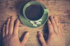 Mann, der Pillen und Kaffee trinkt Stockbild