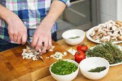 Mann, der Pilze mit Gemüse auf Zählwerk hackt lizenzfreie stockfotos
