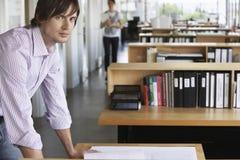 Mann, der Plan im Büro studiert Lizenzfreies Stockbild