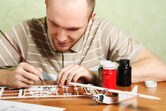 Mann, der Plastikflugzeugbaumuster zusammenbaut Lizenzfreie Stockbilder