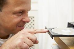 Mann, der Platte in DVD einsetzt Stockfotografie