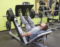 Mann, der Platte geladene Bein-Presse verwendet Stockfotos