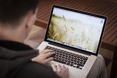 Mann, der Proretina Macbook verwendet Stockfotos