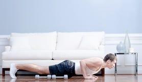 Mann, der Push-ups im Wohnzimmer tut Stockfotos