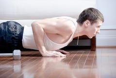 Mann, der Push-ups im Wohnzimmer tut Stockfotografie