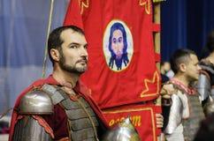 Mann in der Rüstung eines alten russischen Kriegers nahe der roten Fahne mit dem Bild von Christus der Retter Lizenzfreie Stockbilder
