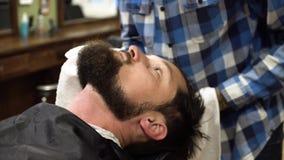 Mann, der Rasur am Friseursalonabschluß oben hat Berufsfriseur, der gerades Rasiermesser mit Gel der scharfen Klinge und der Crem stock footage
