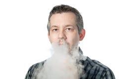 Mann, der Rauch ausatmet stockbild