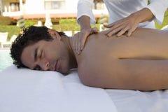 Mann, der Rückenmassage am Badekurort empfängt Lizenzfreies Stockbild