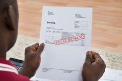 Mann, der Rechnung mit Endnachfrage-Mitteilung hält Lizenzfreie Stockbilder