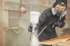 Mann in der Respiratormaske, die hölzerne Planken an der Werkstatt malt Lizenzfreie Stockbilder