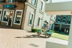 Mann, der Retro- Roller auf Straße reitet Stockbilder