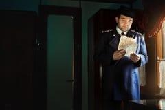 Mann in der Retro- Uniform steht am Fenster und hält Manuskript lizenzfreie stockfotos